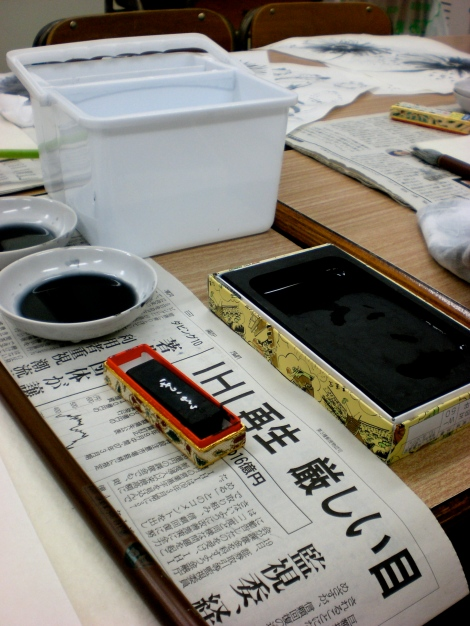 the materials - the small black stick is the sumi (the black ink), and we sort of grind it with water in the black stone to make the paint