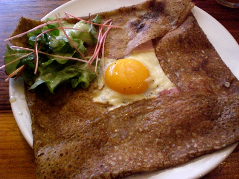 A buckwheat crepe with ham, cheese, and an egg. Served with a small salad.